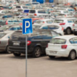 Blur image of parking next to modern shopping mall at peak hour, for background. Blurred uncovered parking of retail store in background. With place for your royalty free stock photo