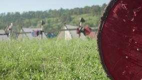 Blur of man with sward preparing for reenactment of ancient battle. Focused knight`s shield on the right stock video footage