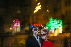 Blur. A man and a woman with a visage, a pattern of skulls, a zombie on the face. Dead at night. A pair of zombies in the dark out stock images