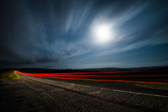 Vehicle lights on a road at night. Red time lapse blur of vehicle lights driving on a road at night with the moon in the background stock image