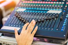Blur Photo Hand adjusting audio mixer. sound engineer hands working on sound mixer in live concert. DJ controlled the sound system by mixer equalizer in stock photography