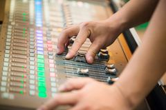 Blur Photo Hand adjusting audio mixer. sound engineer hands working on sound mixer in live concert. DJ controlled the sound system by mixer equalizer in royalty free stock images
