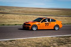 Orange race car on track. Blur of racing orange car on rural track on sunny day Royalty Free Stock Photography