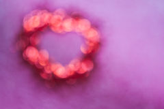 Blur of red bokeh with heart shape inside on pink background Royalty Free Stock Photos