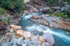 Blur of river over rocks. Blur of river water over stones on sunny day Stock Photo