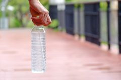 A man hand holding a bottle of cool drinking water. With blur small bridge ground floor at the green park royalty free stock image