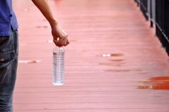 A man hand holding a bottle of cool drinking water. With blur small bridge ground floor and wet floor royalty free stock photography