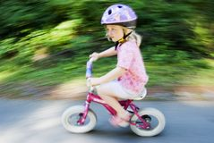 Blur of small child on bike Stock Photo