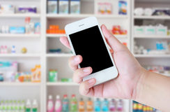 Blur some shelves of drug in the pharmacy drugstore. Pharmacist hand holding smart phone in the pharmacy Stock Photo