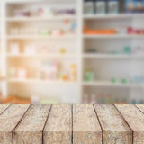 Blur some shelves of drug in the pharmacy drugstore. Wood table on blur some shelves of drug in the pharmacy drugstore Royalty Free Stock Photo