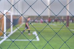 Blur of playing football. Blur of someone playing football in the football field behind the net stock photos