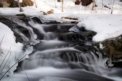 Blur of stream with snowy banks royalty free stock image