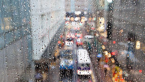 Blur traffic view through a window covered in rain Stock Photos