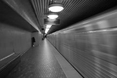 Blur Train. A high speed subway car flys by. Black & white image, with extra grain for an urban gritty feel Stock Photos