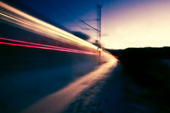 Blur of train at dusk in snow. The blurred lights and blowing snow of a passing train after sunset Stock Images
