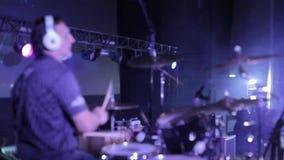 blur Vista lateral de un batería profesional que se realiza en etapa iluminación del concierto Proyectores en el fondo almacen de metraje de vídeo