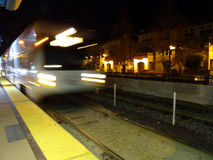 Blur of VTA transit lightrail train arrives into station at nigh royalty free stock photo
