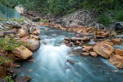 Blur of water on river. Blur of water flowing in river with rocky banks on sunny day Stock Photos