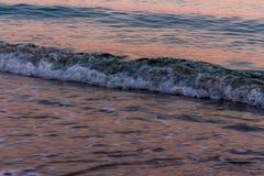 blured波浪 在海水反映的日出颜色 免版税库存照片