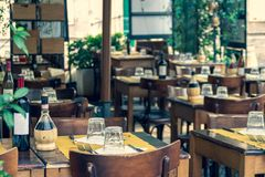 Blured background of cozy italian open air restaurant terrace with served wooden tables and chairs stock photo