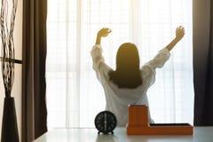 Blured de refrescar mulheres asiáticas estica preguiçoso no quarto após acordar em 6 horas na manhã, despertador, vista traseira imagens de stock royalty free