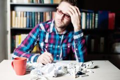 Blured depressed tired man holding his head. Blured depressed tired man in casual cloth and glasses holding his head Royalty Free Stock Photo