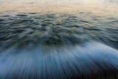 blured fala Wschodów słońca kolory odbijający w wodzie morskiej obraz stock