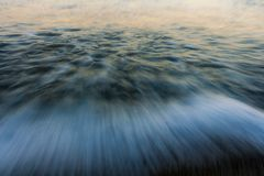 blured golf Zonsopgangkleuren in het zeewater worden weerspiegeld dat stock afbeelding