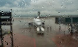 Blured image of airplane at the terminal gate ready for takeoff - Modern international airport on rainy day royalty free stock photo
