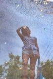 Blured odbicie młoda dziewczyna w kałuży po deszczu Obrazy Royalty Free