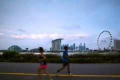 Blured people running in park at Marina Bay morning. Healthy lifestyle Royalty Free Stock Images