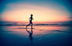 Blured silhouette of a woman jogger on the beach at sunset Royalty Free Stock Images