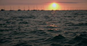 Blured-Wellen Sonnenuntergang-Dock-Pier, Boote und Yachtbewegung im Wasser in der goldenen Zeitlupe des Sonnenuntergangs 4k stock video footage