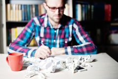 Blured Young man working and thinking in the library. Blured Young man in casual cloth and glasses working and thinking in the library Royalty Free Stock Images