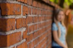 Bluredmeisje die zich dichtbij de bakstenen muur en het wachten bevinden blured achtergrond Stock Afbeelding