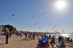 Bluring-Sonne scheint über dem sandigen Strand, wohin Dutzende Drachen fliegen Stockfoto