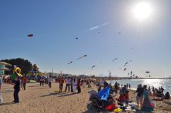 Bluring sun shines over the sandy beach where dozens of kites are flying Stock Photo
