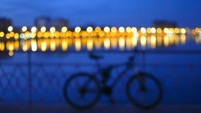 Blurred由桥梁篱芭定了调子与被弄脏的城市光的背景与在河和自行车剪影的反射 库存照片