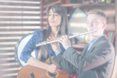 Blurred переэкспонировало фото для пользы предпосылки Парень в костюме с каннелюрой, девушка в голубом платье с гитарой ретро тип стоковые фото