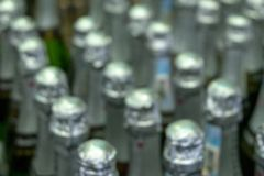 Blurred. Abstract background of bottlenecks with wine or champagne. Rows of bottles in a warehouse or supermarket royalty free stock images