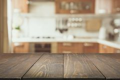 Blurred background. Modern kitchen with tabletop and space for you. Blurred abstract background. Modern kitchen with empty wooden tabletop for display or royalty free stock photography