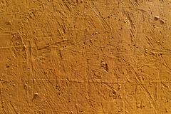 Blurred abstract background. The texture of a painted concrete rough surface with cracks and holes orange color. Cropped shot, horizontal, place for text stock photo