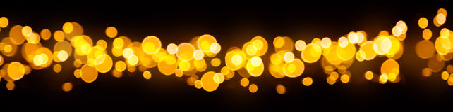 Blurred abstract golden spot lights on black background. Blurred abstract golden spot lights isolated on black background stock photo