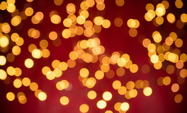 Blurred abstract golden spot lights. Blurred Christmas abstract golden spot lights with soft red background stock images