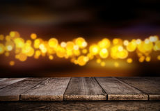Blurred abstract golden spot lights with wood. Blurred abstract golden spot lights isolated on black background. Empty wooden planks on background, ideal for royalty free stock photo