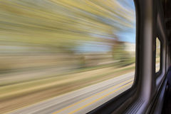 Blurred abstract landscape from train window. Travel concept - blurred abstract landscape with autumn trees and a road seen from a  train window in motion Stock Photos