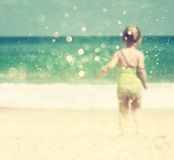 Blurred abstract photo of cute kid standing at the beach looking forward to sea waves Stock Photo
