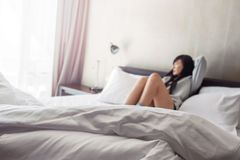 Blurred of Asian Woman sitting relaxed on bed. In Morning, Think and Look outside Stock Images