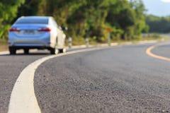 Blurred back side of new silver car parking on the asphalt road. Focus on road Stock Images