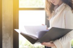 Blurred backgroud effect photo of Young businesswoman at workplace and reading paper in office. business woman wearing suit. Holding documents in Hand stock photography